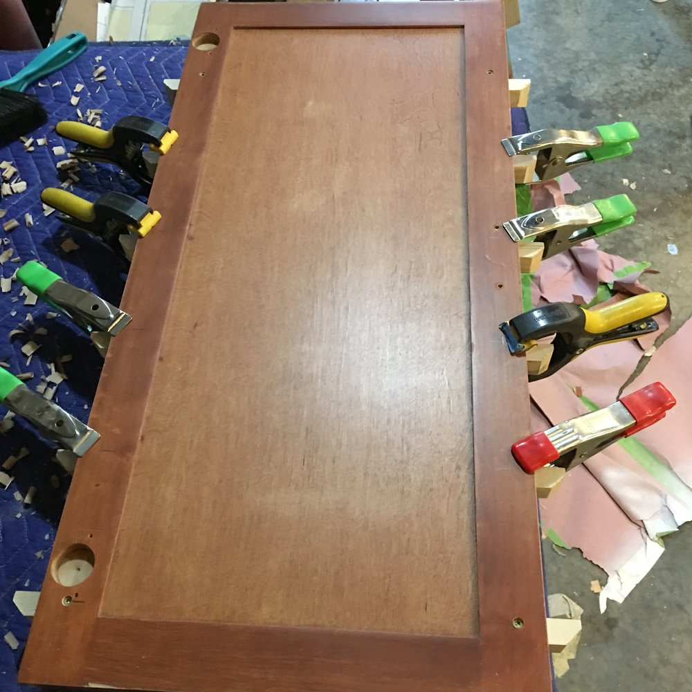 Use clamps to hold boards in place and then drive screws into the shelf boards from the back of the cabinet door.