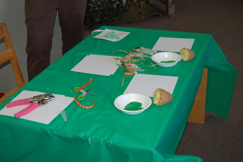 green table cloth covering table with craft supplies