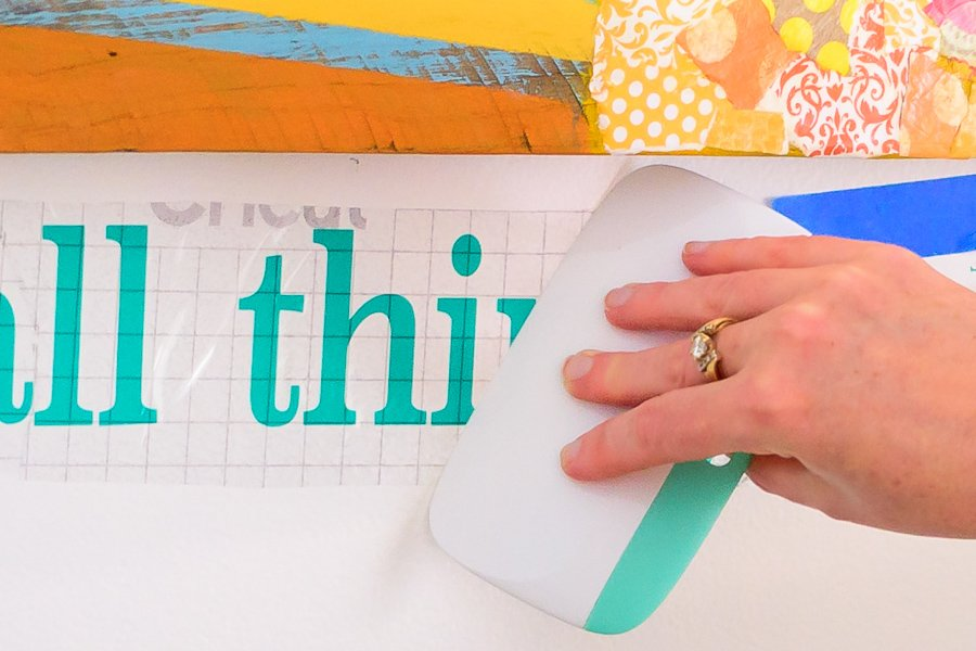 Use cricut xl scraper to adhere phrase to the wall