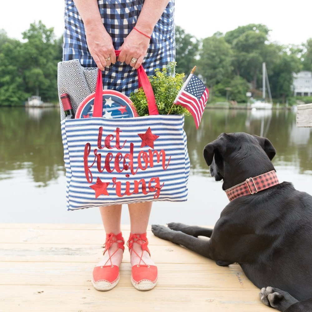 woman holding let freedom ring bag on dock with black dog