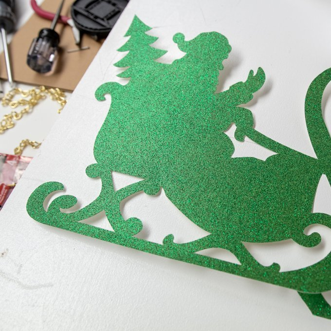 place two sheets of glitter cardstock on a 12x24 Standard Grip mat and cut the same santa sleigh image