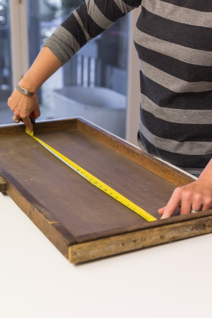 woman measuring wooden tray