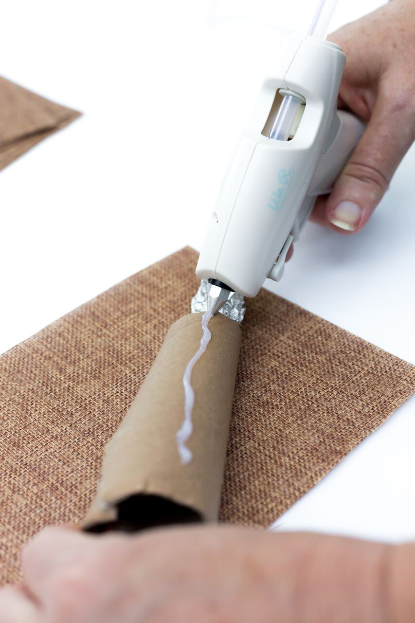apply hot glue along the top of the tube then roll the burlap until it covers the tube