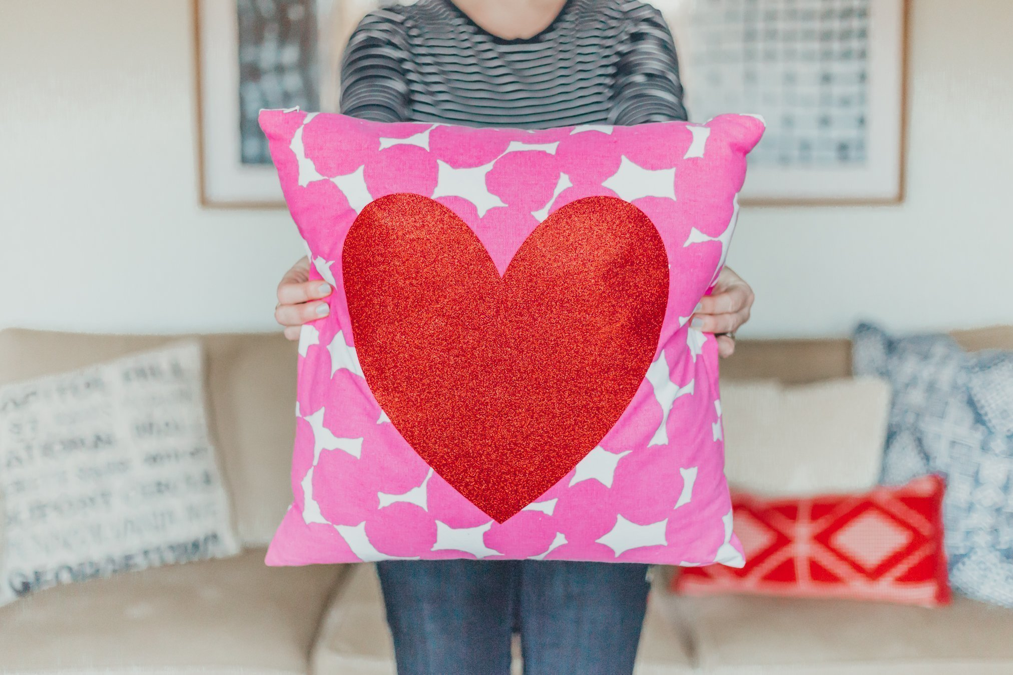 woman holding Valentine's Day pillow