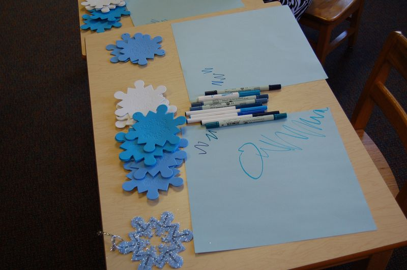 foam snowflakes on table with paper and markers