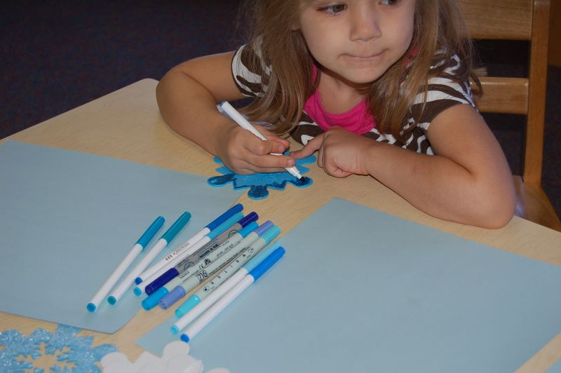 little girl at table coloring snowflake