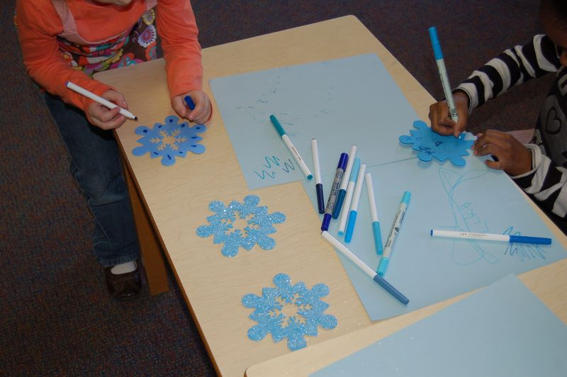 kids at table coloring snowflakes and paper