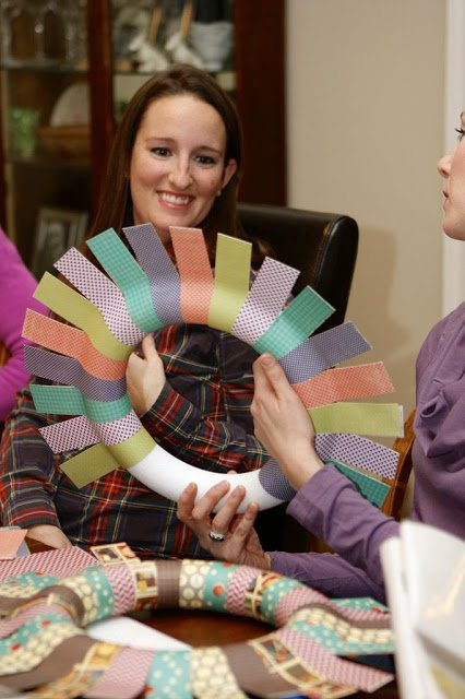 woman looking and smiling at paper wreath