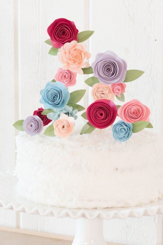 paper flower cake topper on white cake close up
