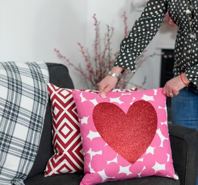 woman fixing Valentine's Day pillow