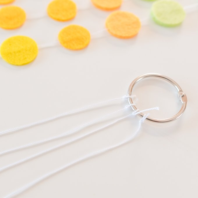 cut three or four lengths of string, tie to smaller ring, then tie other end to large ring and trim excess string