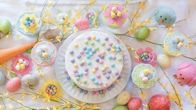 white cake, flowers, and birds on bright spring Easter table