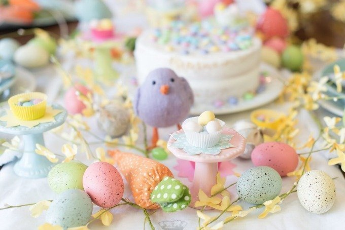purple bird, Easter eggs, and white cake on bright spring Easter table