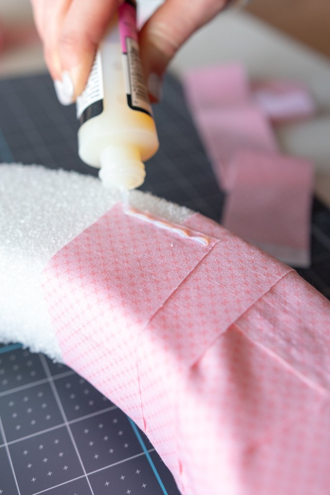 use liquid glue to adhere pink fabric strips to the back of the wreath