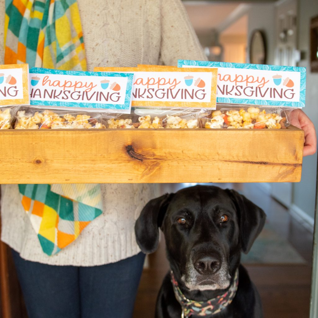 woman holding happy thanksgiving popcorn bags with black dog