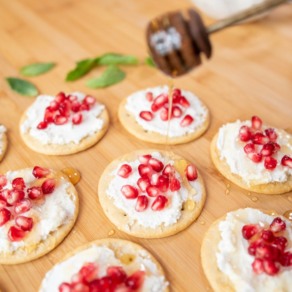 top crackers with pomegranate arilis and honey