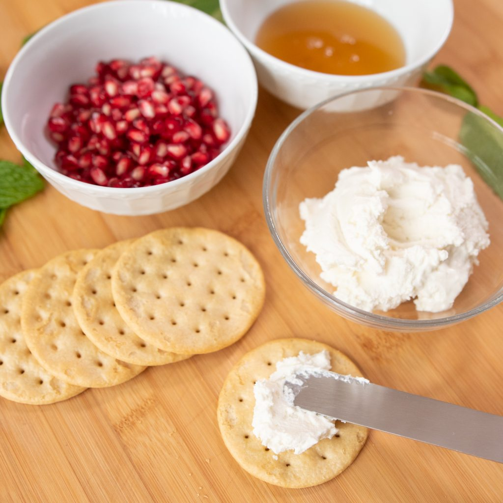 spread goat cheese on crackers